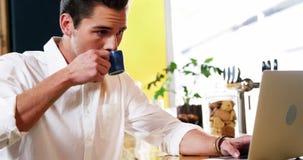 Cliente masculino que usa el ordenador portátil mientras que comiendo café en el contador almacen de metraje de vídeo