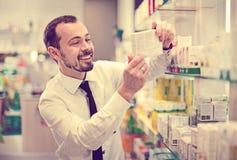Cliente masculino sonriente que busca la medicina correcta Imagen de archivo