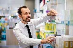 Cliente masculino sonriente que busca la medicina correcta Foto de archivo libre de regalías