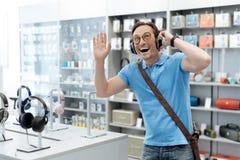 Cliente muito emocional que escuta a música na loja da eletrônica imagem de stock royalty free