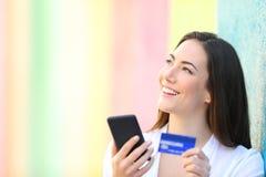 Cliente online che pensa tenendo telefono e la carta di credito fotografia stock libera da diritti