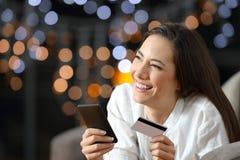 Cliente online pensieroso che tiene una carta di credito immagine stock libera da diritti