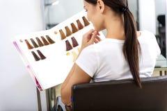 Cliente pensativo que escolhe a cor no barbeiro imagens de stock royalty free
