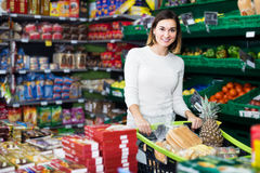 Cliente positivo de la muchacha que busca los dulces sabrosos en supermercado Fotografía de archivo