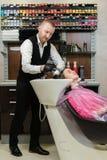 Cliente principal de lavagem do cabeleireiro do homem o champô fora da cabeça de um cliente fotografia de stock royalty free