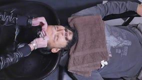Cliente principal que se lava del peluquero en la opinión superior a cámara lenta de la barbería almacen de metraje de vídeo