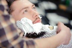 Cliente que afeita en la peluquería de caballeros fotografía de archivo