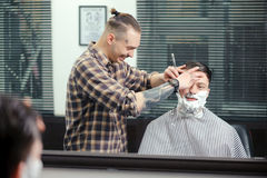 Cliente que afeita en la peluquería de caballeros imagen de archivo libre de regalías