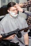Cliente que afeita en la peluquería de caballeros imágenes de archivo libres de regalías