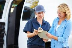 Cliente que assina para a entrega do correio fêmea Foto de Stock Royalty Free
