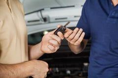 Cliente que da llave del coche al mecánico Imagen de archivo libre de regalías