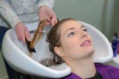 Cliente que descansa quando cabelo que está sendo limpado Imagem de Stock Royalty Free