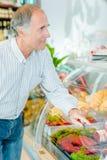 Cliente que elige la carne en el ` s del carnicero Foto de archivo libre de regalías