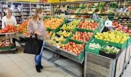 Cliente que escolhe frutos na loja de mantimento fotos de stock royalty free