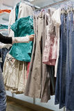 Cliente que escolhe a roupa da cremalheira da loja Foto de Stock