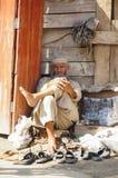 Cliente que espera del zapatero para en Paquistán Imagenes de archivo
