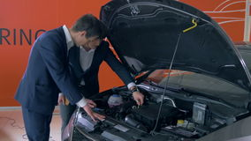 Cliente que examina el motor de coche metrajes