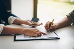 Cliente que firma un documento de papel para la casa de compra Agente de la propiedad inmobiliaria foto de archivo libre de regalías