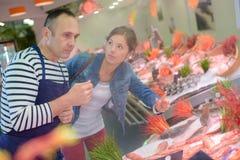 Cliente que habla con el pescadero Imagen de archivo