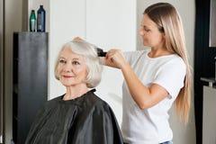 Cliente que hace que el pelo sea enderezado por el peluquero Foto de archivo