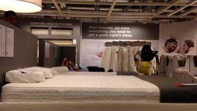 Cliente que intenta el nuevo colchón dentro de la tienda de Ikea metrajes