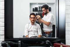 Cliente que mira muy cuidadosamente para los prosess de peinar el pelo Fotos de archivo