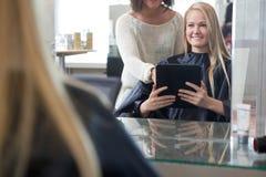 Cliente que muestra estilo de pelo en la tableta de Digitaces Imagen de archivo libre de regalías