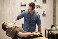 Cliente que obtém a barba que barbeia na barbearia Fotografia de Stock