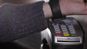 Cliente que paga com tecnologia de NFC pelo relógio esperto sem contato no terminal no café moderno Fotografia de Stock Royalty Free