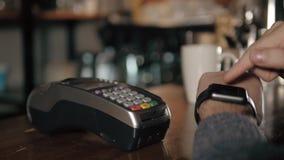 Cliente que paga com tecnologia de NFC pelo relógio esperto sem contato no terminal no café moderno Fotografia de Stock