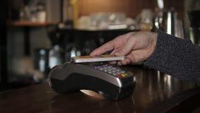 Cliente que paga com tecnologia de NFC pelo telefone celular no terminal no café moderno Fotos de Stock Royalty Free