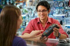 Cliente que paga con la tarjeta de crédito en tienda de informática china Imágenes de archivo libres de regalías