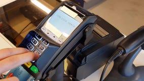 Cliente que paga con la tarjeta en el terminal del pago Fondos de las finanzas del negocio almacen de video
