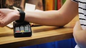 Cliente que paga con tecnología de NFC por el reloj elegante sin contacto en el terminal en café moderno metrajes