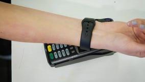 Cliente que paga con tecnología de NFC por el reloj elegante sin contacto en el terminal en café moderno almacen de metraje de vídeo
