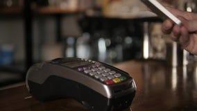 Cliente que paga con tecnología de NFC por el teléfono móvil en el terminal en café moderno almacen de metraje de vídeo