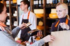 Cliente que paga pela ordem de queijo na loja de mantimento imagens de stock royalty free