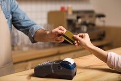 Cliente que paga por la tarjeta de crédito en café fotos de archivo libres de regalías