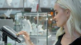 Cliente que paga su orden con una tarjeta de crédito en una alameda de compras máquina y vuelta del lector de la tarjeta de crédi almacen de metraje de vídeo