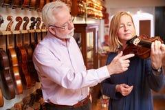 Cliente que prueba el violín en Music Store Foto de archivo libre de regalías
