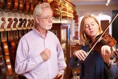 Cliente que prueba el violín en Music Store Imagen de archivo libre de regalías