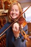 Cliente que prueba el violín en Music Store Fotos de archivo libres de regalías