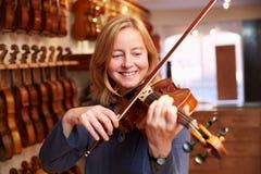 Cliente que prueba el violín en Music Store Fotos de archivo