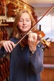 Cliente que prueba el violín en Music Store Imagenes de archivo