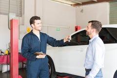 Cliente que recebe a chave do carro do reparador At Garage imagem de stock