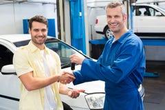 Cliente que sacude las manos con el mecánico que toma llaves Imagen de archivo libre de regalías