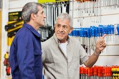 Cliente que señala mientras que mira la tienda del hardware fotos de archivo libres de regalías