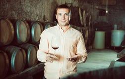 Cliente que sostiene el vidrio de vino de barriles de madera Imagen de archivo