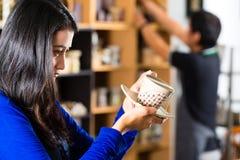 Cliente que sostiene una taza en una tienda de regalos Imágenes de archivo libres de regalías