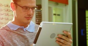 Cliente que usa la tableta digital en tienda óptica almacen de metraje de vídeo